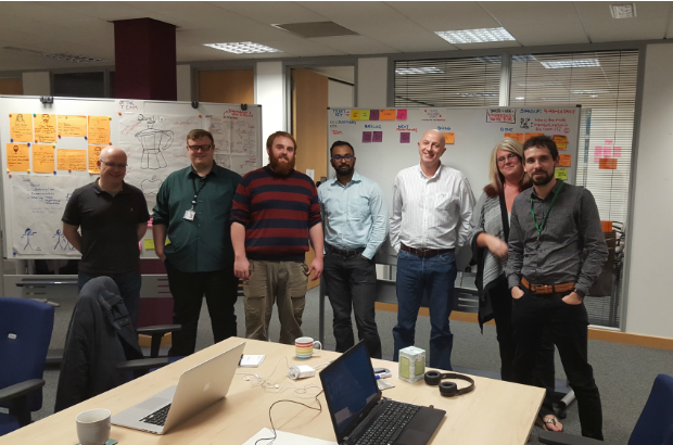 A picture of the current team in the Sheffield Hub, all standing and smiling