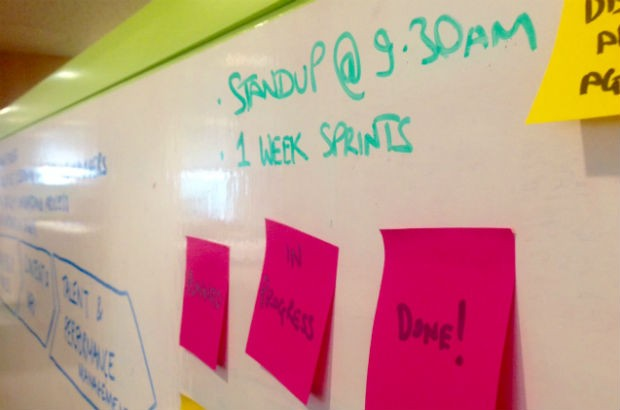 "Picture of a whiteboard which features the text ""Standup @ 9.30am, 1 week sprints"". The board also has postit notes attached to it that say ""Planned"", ""In progress"", and ""Done!"""