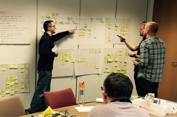 Image of the design sprint in progress - team members at a wall with post its