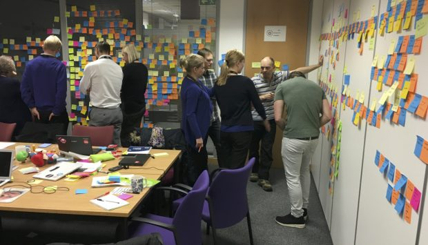 A team crowded round a wall of Post It notes