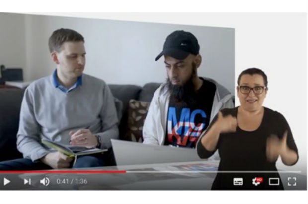 A video still showing a participant being interviewed at home. A signer translates the narration into sign language.