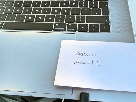 Image of a laptop keyboard with a note stuck to it entitled 'Password: password 1'