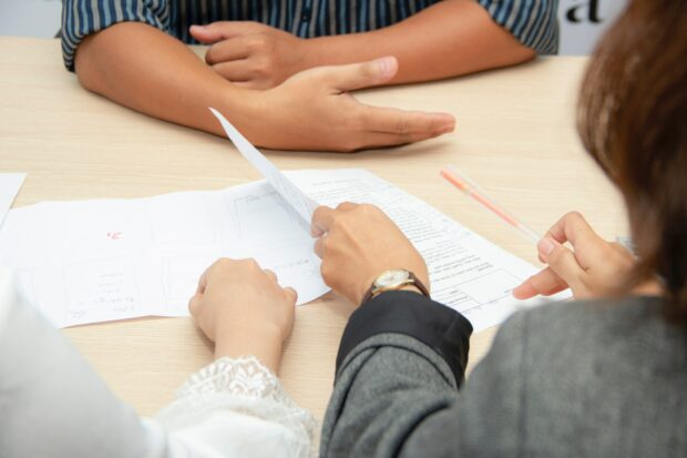 An image of the forearms of three people discussing a proposal